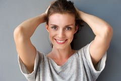 Happy mid adult woman smiling with hands in hair Royalty Free Stock Photography