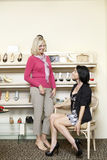 Happy mid adult woman trying on heels while mature female looking in shoe store Stock Image