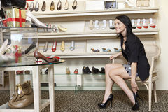 Happy mid adult woman trying high heels in footwear store Royalty Free Stock Images