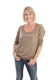 Happy middle age blond woman in blue jeans isolated over white. Royalty Free Stock Photos