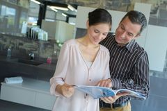Happy middle-age couple with brochure at store. Happy middle-age couple with brochure at a store Stock Photo