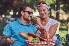 Attractive middle age couple during dating, enjoying a picnic on a bench in the city park. Happy middle age couple during dating, enjoying a picnic on a bench Royalty Free Stock Photography
