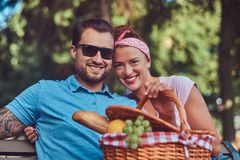 Attractive middle age couple during dating, enjoying a picnic on a bench in the city park. Happy middle age couple during dating, enjoying a picnic on a bench Stock Photos