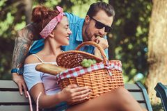 Attractive middle age couple during dating, enjoying a picnic on a bench in the city park. Happy middle age couple during dating, enjoying a picnic on a bench Stock Photo