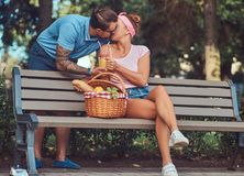Attractive middle age couple during dating, enjoying a picnic on a bench in the city park. Happy middle age couple during dating, enjoying a picnic on a bench Stock Images