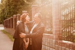 Happy middle-age couple hugging outdoors stock photo