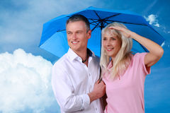 Happy middle age couple looking into the future unter an umbrella stock photos