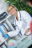 Happy middle-age female doctor in office. Happy middle-age female doctor in her office Stock Image