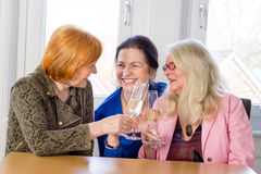 Happy Middle Age Moms Tossing Glasses of Wine. Three Happy Middle Age Mom Best Friends Tossing Glasses of White Wine and Smiling Each Other While Sitting at the Royalty Free Stock Images
