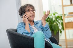 Happy middle age woman with glasses using and talking phone. An happy middle age woman with glasses using and talking phone stock image