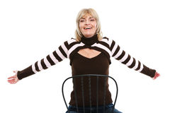Happy middle age woman sitting on chair Royalty Free Stock Photo