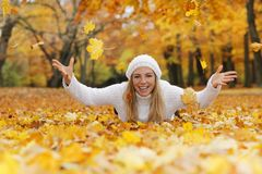 Happy middle age woman throwing yellow autumn leaves royalty free stock photo