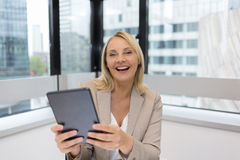 Happy Middle aged business woman using digital tablet. Modern office Stock Photo