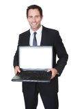 Happy middle aged businessman with laptop Royalty Free Stock Photos