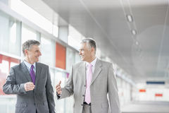 Happy middle aged businessmen talking while walking in railroad station Royalty Free Stock Photography