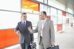 Happy middle aged businessmen talking while walking in railroad station Stock Image