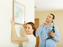 Happy middle-aged couple choosing place for picture. In the wall at home Stock Photos