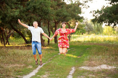 Happy middle-aged couple jumping outdoors. Stock Photos