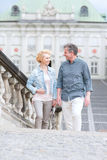 Happy middle-aged couple looking at each other while climbing steps Royalty Free Stock Photos