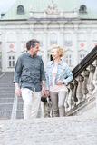 Happy middle-aged couple looking at each other while climbing steps royalty free stock photo