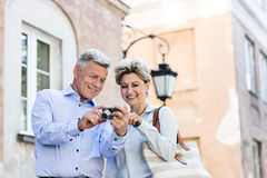 Happy middle-aged couple looking at pictures on digital camera in city Royalty Free Stock Images