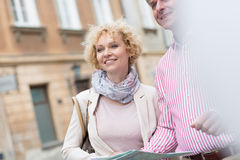 Happy middle-aged couple with map in city Stock Image