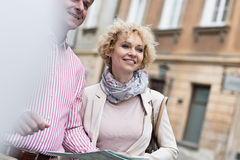 Happy middle-aged couple with map in city Royalty Free Stock Photo