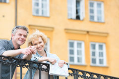 Happy middle-aged couple with map leaning on railing against building Stock Images