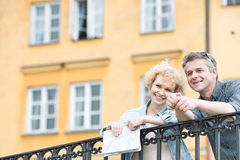 Happy middle-aged couple with map leaning on railing against building Royalty Free Stock Images