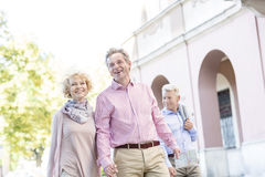 Happy middle-aged couple with map walking in city Royalty Free Stock Images
