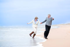 Happy middle aged couple running on a beach. Holding hands and jumping away from the waves stock images