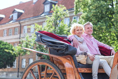 Happy middle-aged couple sitting in horse cart on city street Stock Images