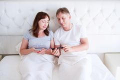 Happy middle aged couple smiling and chating on mobile phone in bedroom, smile people stock photos