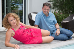 Happy middle aged couple spending romantic time by pool Royalty Free Stock Image