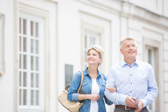 Happy middle-aged couple standing with arm in arm outside building Royalty Free Stock Images