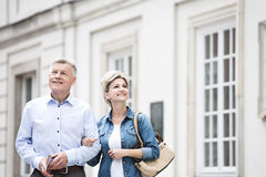 Happy middle-aged couple standing with arm in arm outside building stock photography