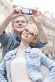 Happy middle-aged couple taking self portrait outdoors Royalty Free Stock Photography