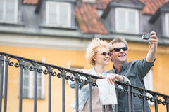 Happy middle-aged couple taking selfie against building Stock Photo