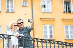 Happy middle-aged couple taking selfie through camera against building Royalty Free Stock Photos