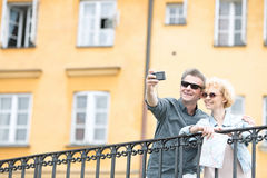 Happy middle-aged couple taking selfie through camera against building Royalty Free Stock Photography