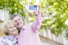 Happy middle-aged couple taking selfie through mobile phone outdoors Stock Images