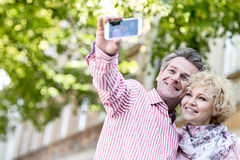 Happy middle-aged couple taking selfie through mobile phone outdoors Stock Image