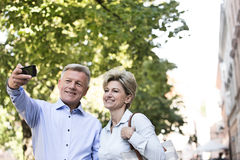 Happy middle-aged couple taking selfie outdoors Stock Image