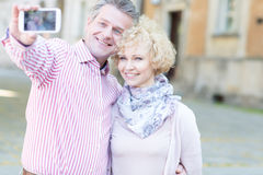 Happy middle-aged couple taking selfie through smart phone in city Stock Photography