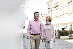 Happy middle-aged couple talking while walking in city Stock Images