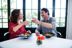 Happy middle-aged couple toasting champagne flutes while having lunch Stock Photography