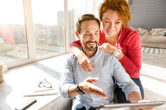 Happy middle aged couple using gadgets at home Stock Photos