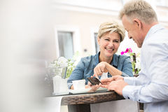Happy middle-aged couple using mobile phone at sidewalk cafe Royalty Free Stock Photography