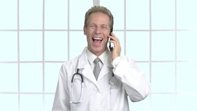 Happy middle-aged doctor talking on phone. stock video