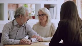 Happy middle aged family couple meeting female real estate agent.